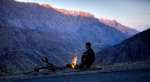 A Kurdish man settles in for a night of guarding some roadworking machinery in the mountains near the Iran/Iraq border. The border is rife with smugglers who carry alcohol from Iraq (where alcohol is legal) into the villages on the Iranian side. From there it is transported by vehicle to the cities. In Tehran a can of beer on the black market fetches around $10USD.