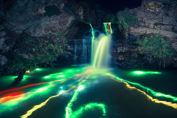 Colorful Long Exposure Photos of Glow Sticks Dropped Into Waterfalls