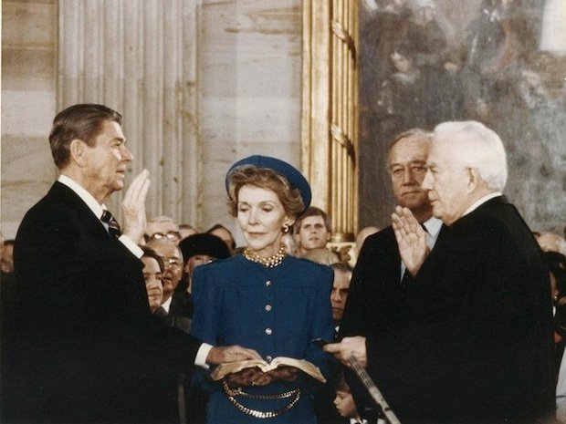 Ronald Reagan taking the oath of office while his wife Nancy holds the Bible for him.