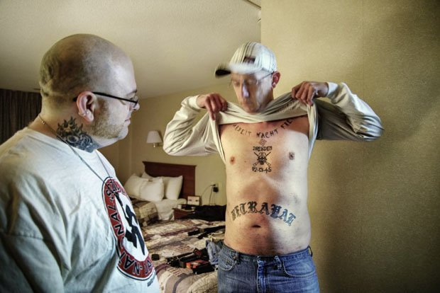 "An NSM member displays his tattoos.  Below the tattoo of remembrance of the bombing of Dresden, is written ""Betrayal"""