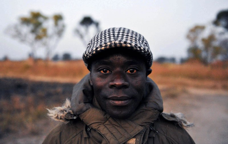 A middle-aged farmer with red eyes poses for the camera in the village of Chilonda