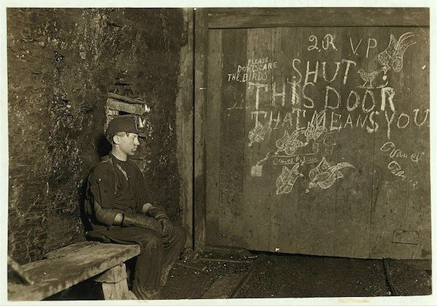 Vance, a Trapper Boy, 15 years old. Has trapped for several years in a West Va. Coal mine. $.75 a day for 10 hours work. All he does is to open and shut this door: most of the time he sits here idle, waiting for the cars to come. On account of the intense darkness in the mine, the hieroglyphics on the door were not visible until plate was developed. Location: West Virginia.