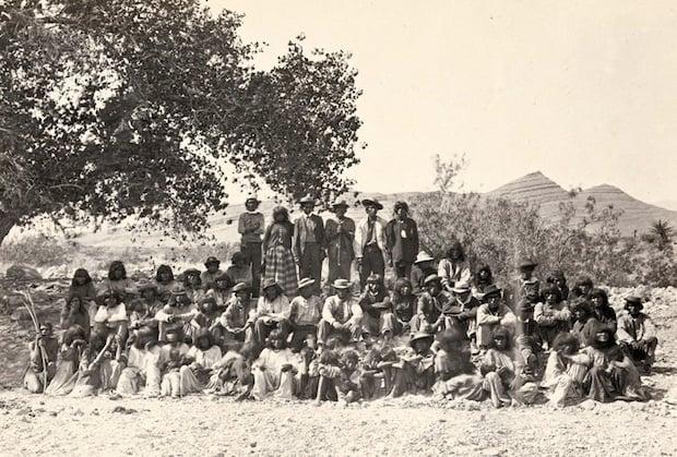 Native American (Paiute) men, women and children posing under a tree near Cottonwood Springs (Washoe County), Nevada. Taken in 1875.