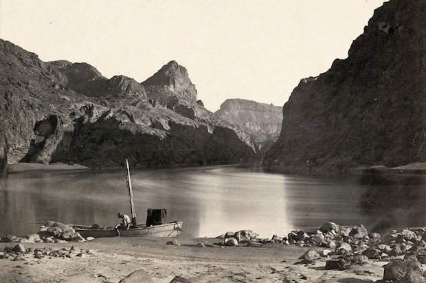 Man in a wooden boat on the edge of the Colorado River in the Black Canyon, Mojave County, Arizona. Taken in 1871.