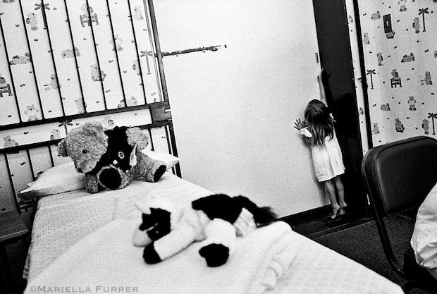 "A young girl attempts to get out of the room where she is to have a medical forensic examination after a 9yr old relative admitted to playing sexually ""games"" with her. It was later found that the young boy had himself been abused so they were both sent to counselling. The Teddy Bear Clinic for Abused Children. Johannesburg, March 2003"