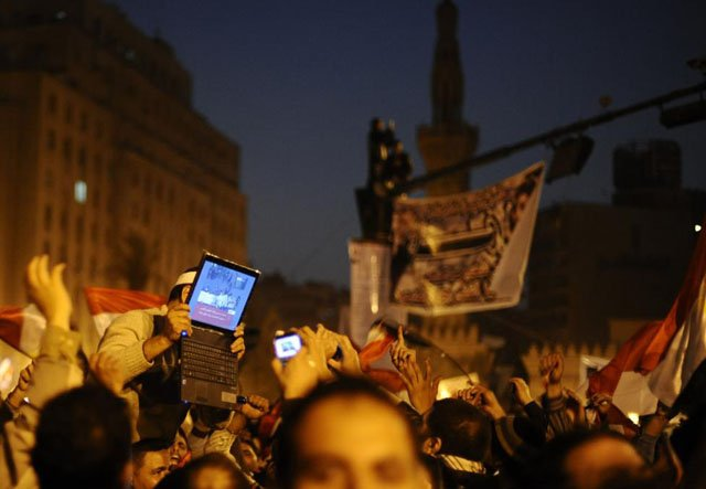 An opposition supporter holds up a laptop showing images of celebrations in Cairo's Tahrir Square, after Egypt's President Hosni Mubarak resigned, February 11, 2011. Dylan Martinez.