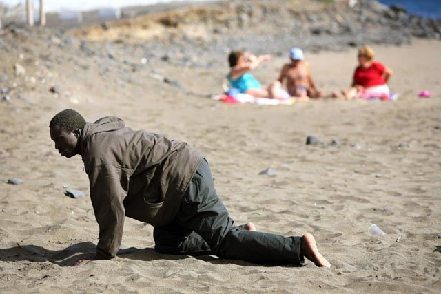 A would-be immigrant crawls on the beach after his arrival on a makeshift boat on the Gran Tarajal beach in Spain's Canary Island of Fuerteventura, May 5, 2006. Juan Medina.