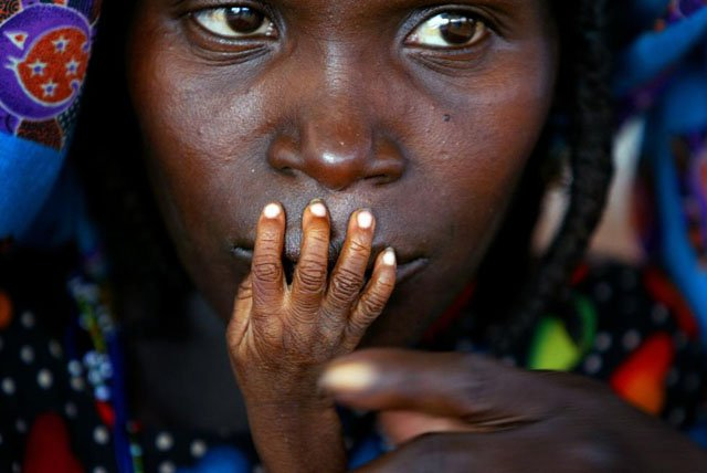 The fingers of malnourished one-year-old Alassa Galisou are pressed against the lips of his mother Fatou Ousseini at an emergency feeding clinic in the town of Tahoua in northwestern Niger, during a drought, August 1, 2005. Finbarr O'Reilly.
