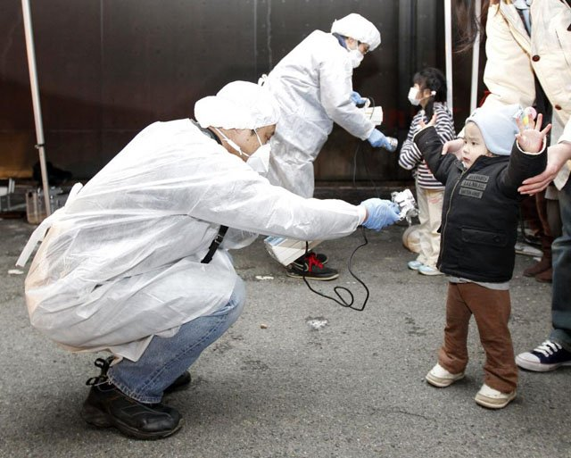 Officials in protective gear check for signs of radiation on children who are from the evacuation area near the Fukushima Daini nuclear plant in Koriyama, Japan, March 13, 2011. Kim Kyung Hoon.