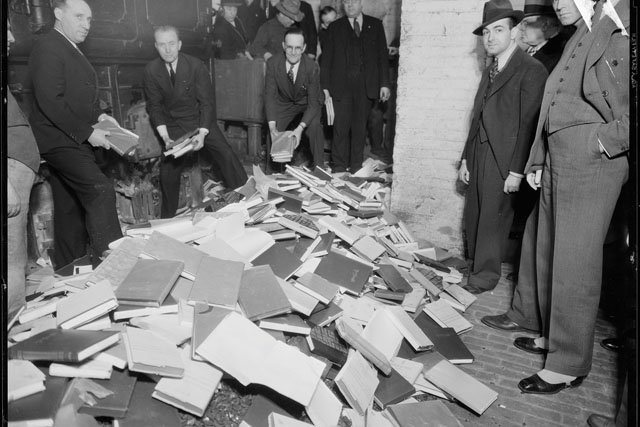 Police destroying indecent books by tossing them into a fire.