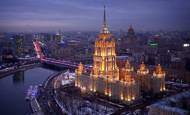 Hotel Ukraina, lit up at dusk.