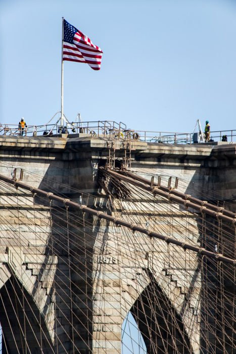 Workers atop of the far tower of the Brooklyn Bridge at a distance of more than half a mile