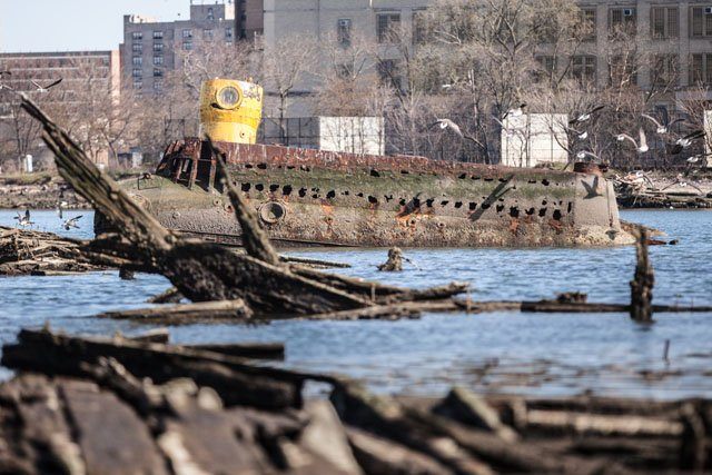 A homemade submarine lies half-submerged in the mud of Coney Island Creek in Brooklyn.  The vessel became lodged in the muck shortly after embarking on a failed treasure hunting expedition in the 1970s.