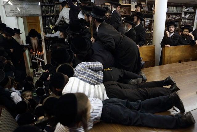 Hasidic Jews watch as their rabbi lights Hanukkah candles.