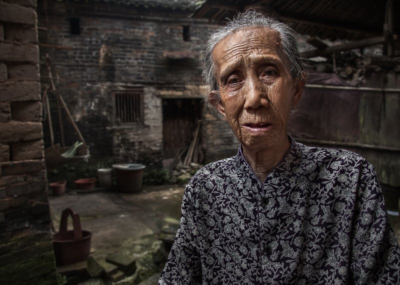 An older, Chinese woman from a small village near XingPing sitting down outside her house.
