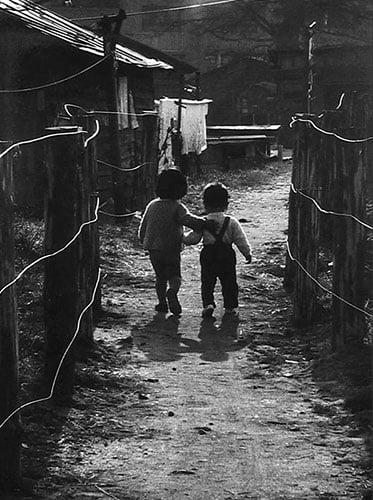 Children walking among makeshift shelters after the bomb. Photo by Kikujiro Fukushima.