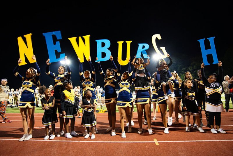 Cheerleaders, big and small, support their team at a home game. Ben Moldenhauer/Photographers For Hope