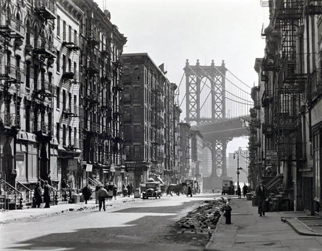 Pike and Henry Streets, Manhattan. Looking down Pike Street toward the Manhattan Bridge, street half in shadow, rubble in gutters, some traffic.