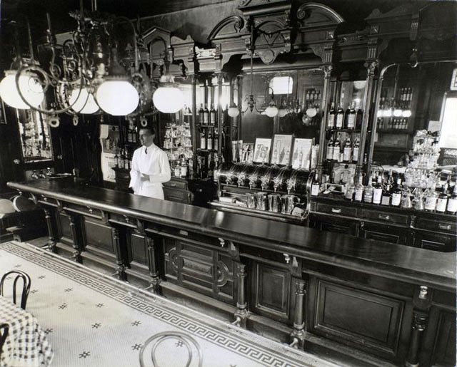 Billie's Bar, 56th Street and First Avenue, Manhattan. Bartender stands behind bar, shelves arrayed with bottles, pitchers and beer spigots, tile floors, lights and mirrors.