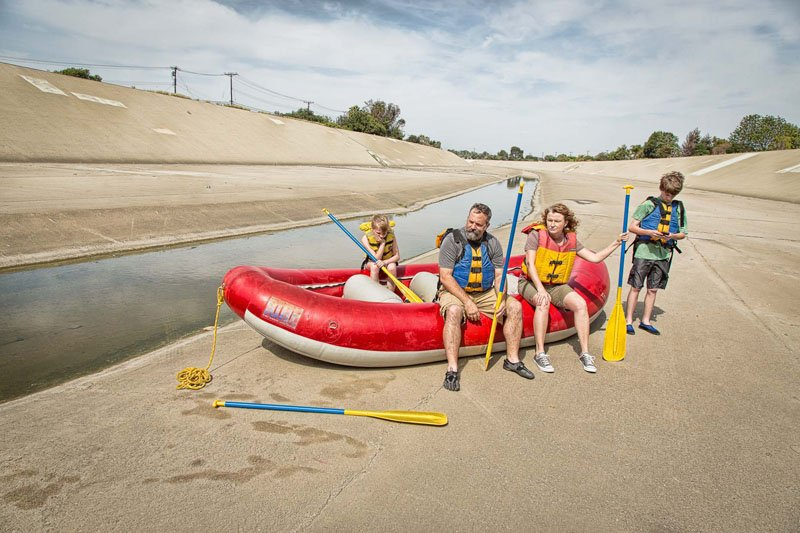 Family with whitewater raft standing next to Coyote Creek storm channel in Long Beach, California.