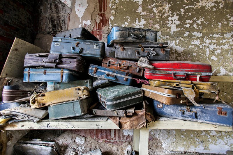 Patient luggage stacked in a top-floor room of an intake administration building. Patients would arrive with personal belongings in the hopes they could enjoy a piece of 'home' while institutionalized; however these belongings would simply be placed into storage.