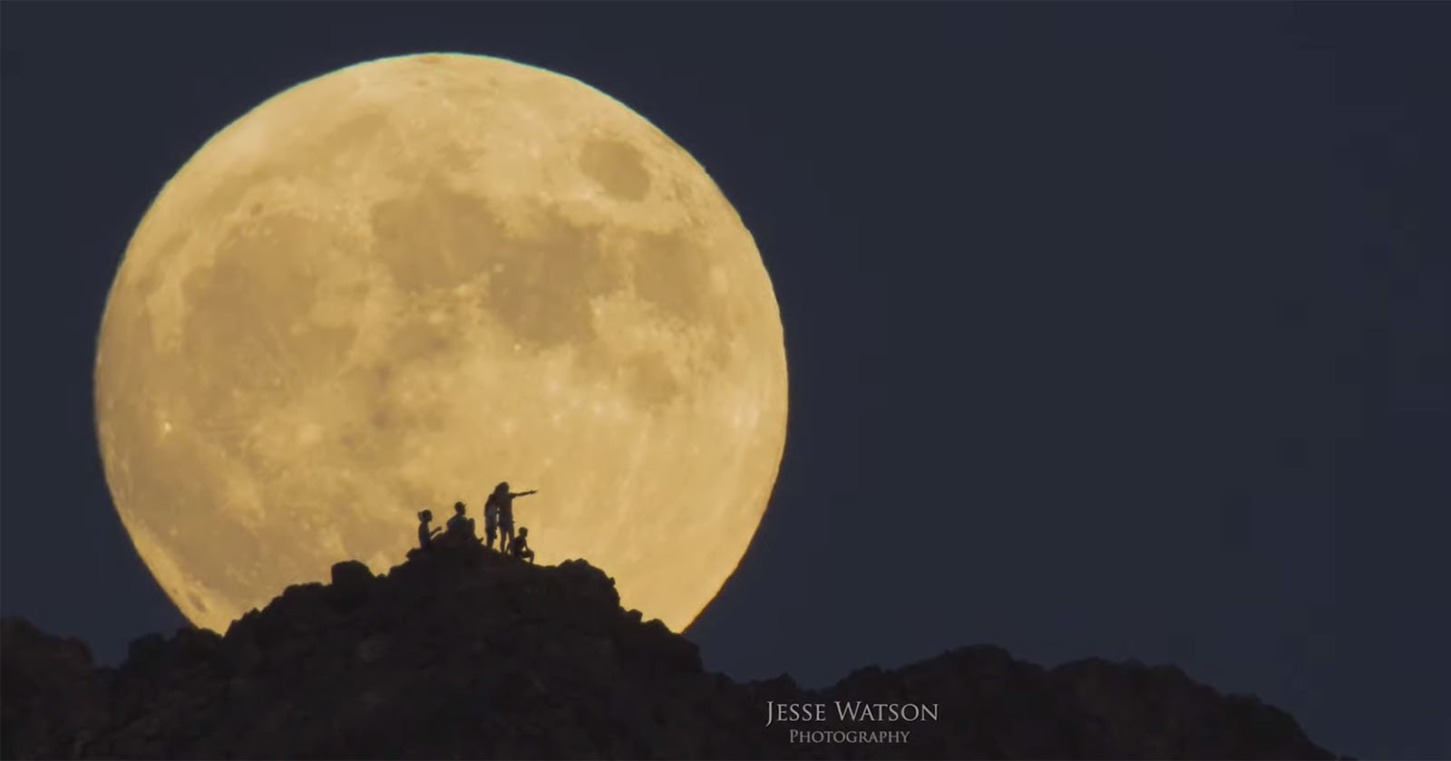 Silhouettes of a Hiking Family Framed Inside a Rising Full Moon
