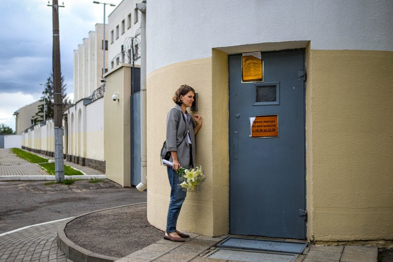 Title: Waiting for Release at a Temporary Detention Center in Belarus © Nadia Buzhan Caption: Olga Sieviaryniec waits for her husband Paval outside a detention center on Akrestsin Street, Minsk, Belarus, on 22 July 2020. Story: Paval Sieviaryniec had been held on remand since 7 June, and his family had learned he was about to be released. Olga waited outside the prison for two hours, but Paval was not freed. Paval Sieviaryniec is a Christian Democrat politician and a well-known political activist. He is one of the founders of Youth Front, a youth movement supporting civil society based on Christian-democratic principles and the free market, and the education of young people to revive Belarusian national culture and language. He was arrested while collecting signatures in support of candidates to stand against President Alexander Lukashenko in his bid for a sixth consecutive term in office. Lukashenko had been in power since 1994. Dubbed 'Europe's last dictator by media outlets, he had frequently repressed opposition, and had not had a serious challenge to his leadership in the previous five elections. Amnesty International considers Paval Sieviaryniec a prisoner of conscience. He was still in prison in early 2021, partly in solitary confinement and unable to meet with a lawyer. He was denied access to books and television, and his Bible was taken from him.